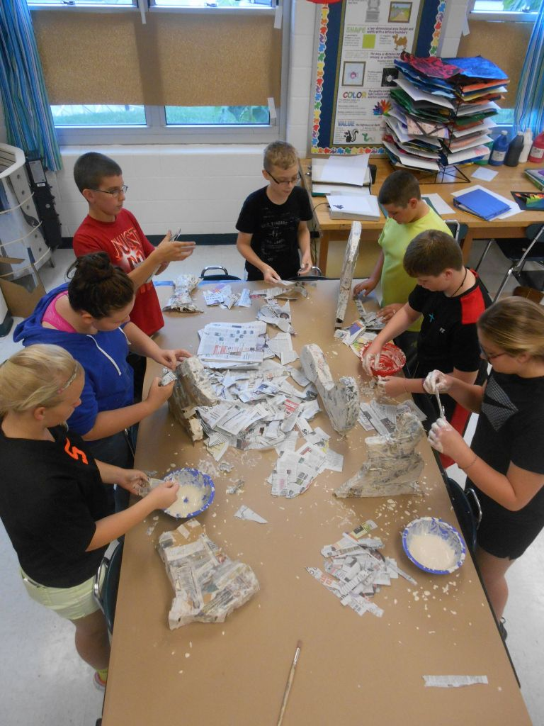 Students working with paper mache on their art projects.