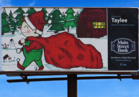 Taylee Sipin's billboard drawing features an elf dragging Santa's big red bag filled with toys. Snowmen and Santa's Workshop is in the background with snow-covered pine trees.